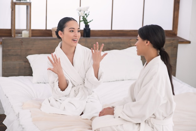 Interessant gesprek. aangename jonge vrouw die naar haar zus kijkt terwijl ze haar een interessant verhaal vertelt
