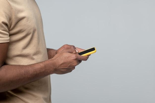 Interessant hier. handen van afro-amerikaanse man in lichte tshirt permanent zijwaarts met smartphone op grijze achtergrond, zonder gezicht