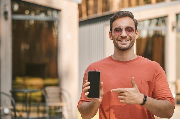 Interessant hier. vrolijk lachende man in zonnebril wijzend met de vinger naar het scherm van de smartphone die buiten staat op een zonnige herfstdag