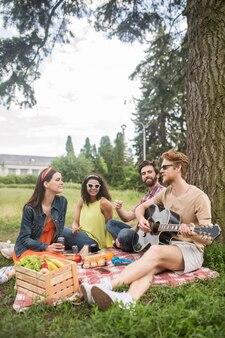 Interessant tijdverdrijf. jonge roodharige man in zonnebril die gitaar speelt en vriendelijke attente vrienden die samen rusten op picknick