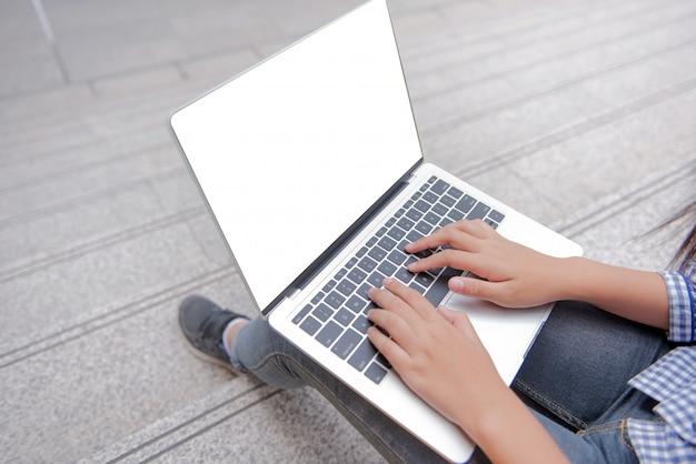 Interessante aziatische meisjes typen, chatten, zitten, chatten, reageren met een laptopapparaat