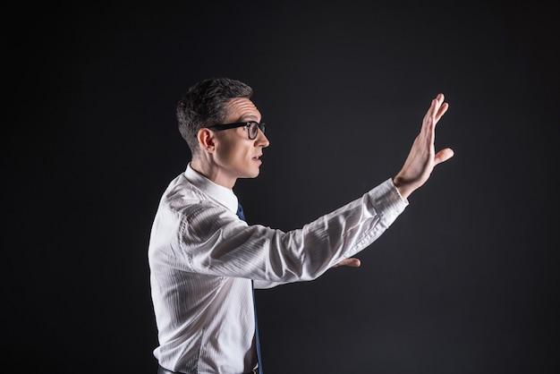 Interessante bezigheid. slimme, aangename serieuze man die naar het sensorische paneel kijkt en zijn hand erop drukt terwijl hij zich op zijn werk concentreert