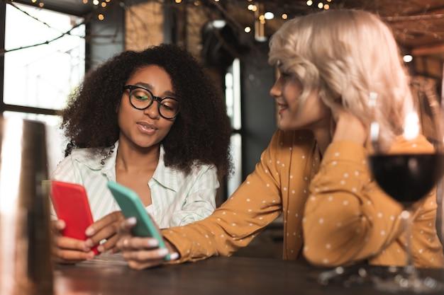 Interessante discussie. mooie jonge vrouwen zitten aan de toog en tonen elkaar vakantiefoto's op hun smartphones terwijl ze erover praten