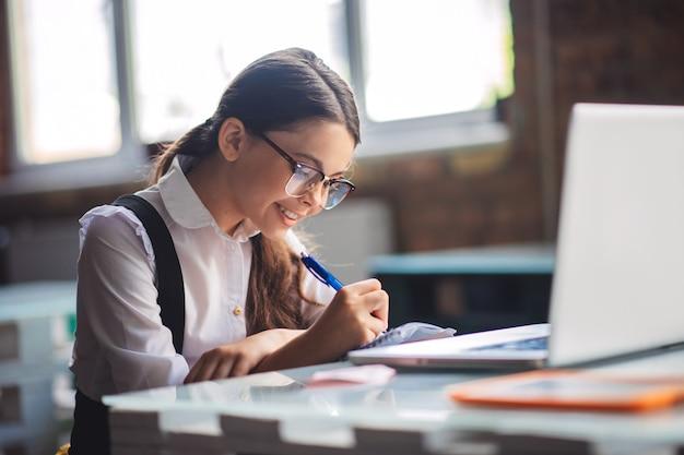 Interessante les. donkerharige schattig meisje studeren en kijken tevreden