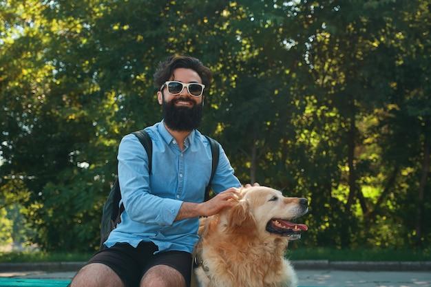 Interessante man zit met zijn hond op de stoel in het park