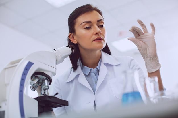 Interessante resultaten. vastberaden jonge onderzoeker die met de microscoop werkt en een monster vasthoudt