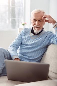 Interessante video. knappe jongeman zittend op de bank in de woonkamer en kijken naar een video op de laptop terwijl hij zijn hoofd op zijn hand laat rusten