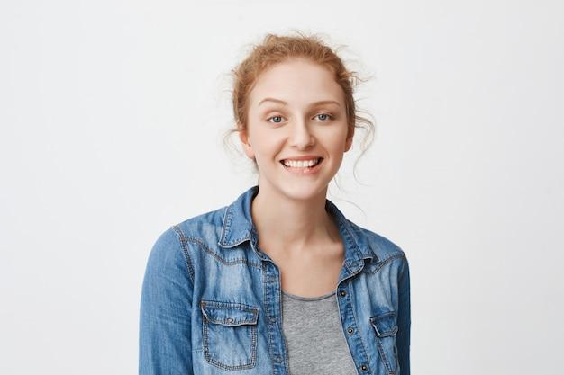 Interessante vrolijke blanke roodharige vrouw met blauwe ogen breed lachend