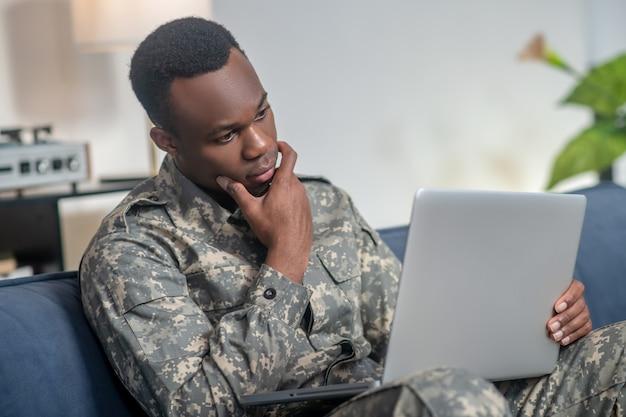 Interesse, informatie. donkere jonge aantrekkelijke man in militair uniform gericht geïnteresseerd kijkend naar laptop zittend op de bank