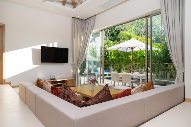Interieur en exterieur ontwerp van woonkamer met uitzicht op het zwembad in luxe villa met zwembad
