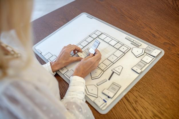 Interieur, indeling van de woning. vrouwelijke handen die verminderde binnenlandse details van een woonkamer boven een plan op een positieve lijst houden.