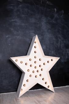 Interieur met een grote houten decoratieve ster met lampen op zwart