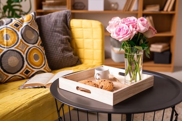 Interieur met kussens en open boek op bank en tafeltje met koekjes, kopje koffie en bos van roze rozen in houten kist