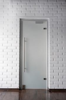 Interieur met matglazen deur op witte bakstenen muur