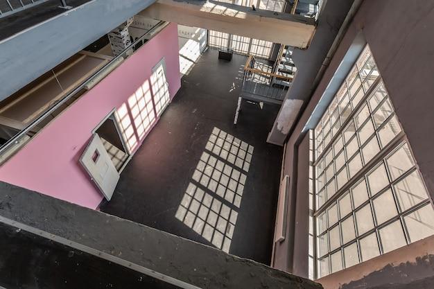 Interieur met meerdere verdiepingen van de open ruimte met grote ramen en roze muren