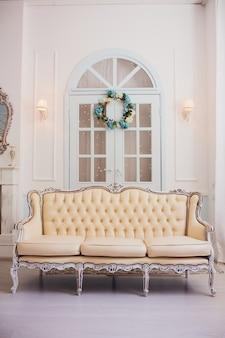 Interieur met vintage meubelen, lichte voorjaarsstudio met mooie witte bank. witte interieur van studio.