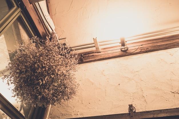 Interieur met wit gedroogd bloemboeket in vaas, moderne rustieke en minimale vintage kamer, licht op de plank, compositie met scandinavische meubels in appartement, minimalistische stijl