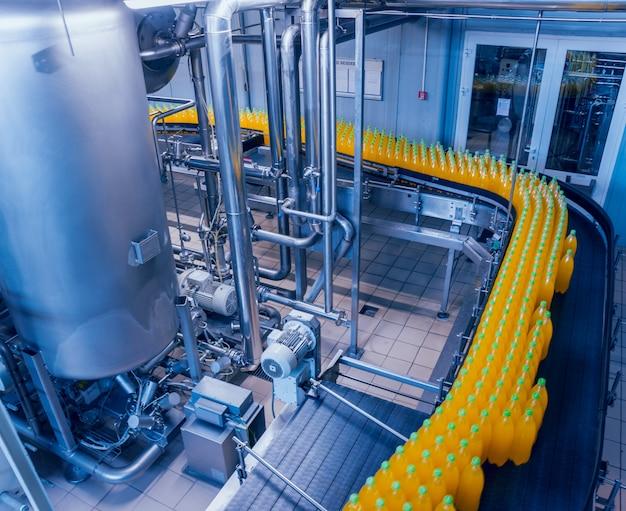 Interieur van de drankfabriek. transportband met flessen voor sap of water. uitrustingen