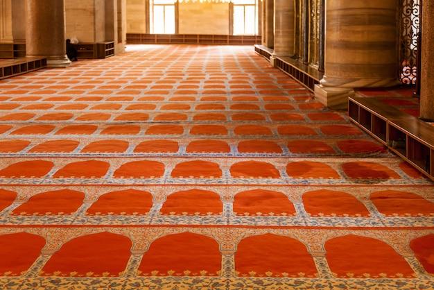 Interieur van de moskee tapijten op de vloer, muurschilderingen op de muren, scheidingswanden met een patroon