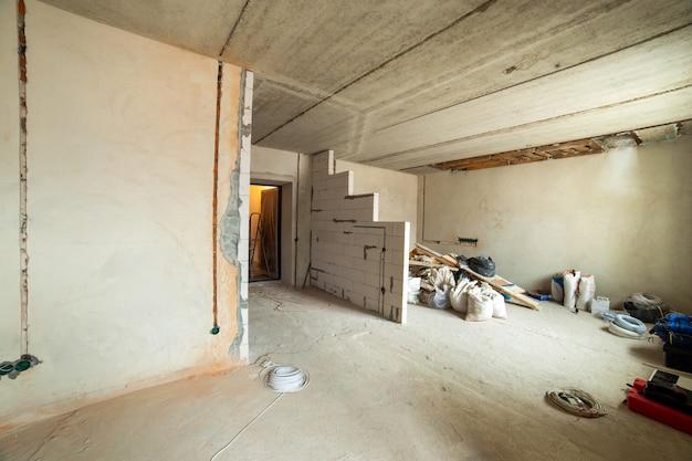 Interieur van een appartementkamer met kale muren en plafond in aanbouw.