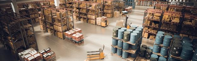 Interieur van een groot magazijn met opgeslagen materiaal en middelen voor het verplaatsen van de pallets.