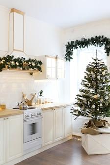 Interieur van een kerst lichte keuken versierd met een kerstboom en slingers
