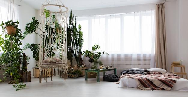 Interieur van een modern studio-appartement met veel planten en een bed op de vloer