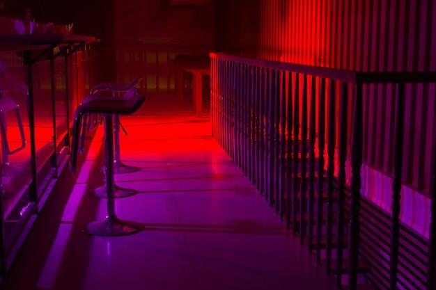 Interieur van een nachtclub met kleurrijke rode en paarse verlichting en een lijn van stijlvolle barkruk langs een reflecterende toog met een reling erachter