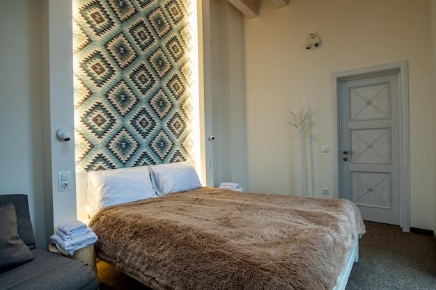 Interieur van een ruime hotel slaapkamer met vers linnen op een groot tweepersoonsbed. gezellige eigentijdse kamer in een modern huis.