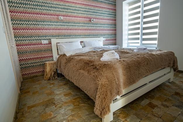 Interieur van een ruime hotelslaapkamer met fris linnengoed op een groot tweepersoonsbed. gezellige eigentijdse kamer in een modern huis.