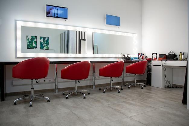 Interieur van een schoonheidssalon met rode stoelen en spiegels