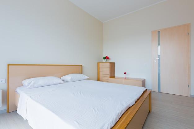 Interieur van een slaapkamer met een groot bed in lichte kleuren