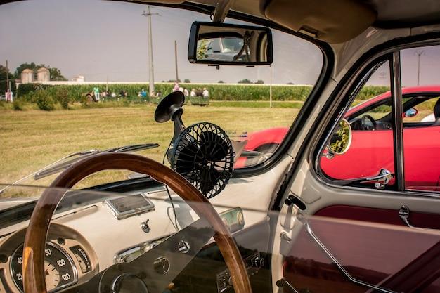 Interieur van een volledig gerestaureerde fiat 500 met het oog op een typisch italiaans landschap. niet zomaar een auto, maar een icoon dat autogeschiedenis heeft geschreven
