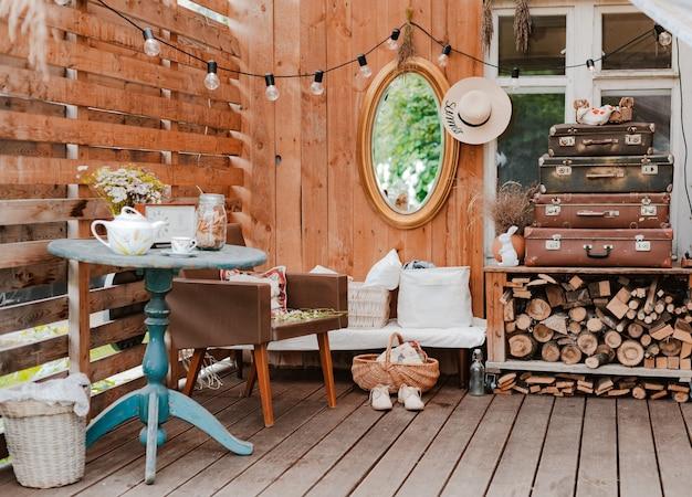 Interieur van het gezellige houten rustieke terras van het zomerland met vintage accessoires