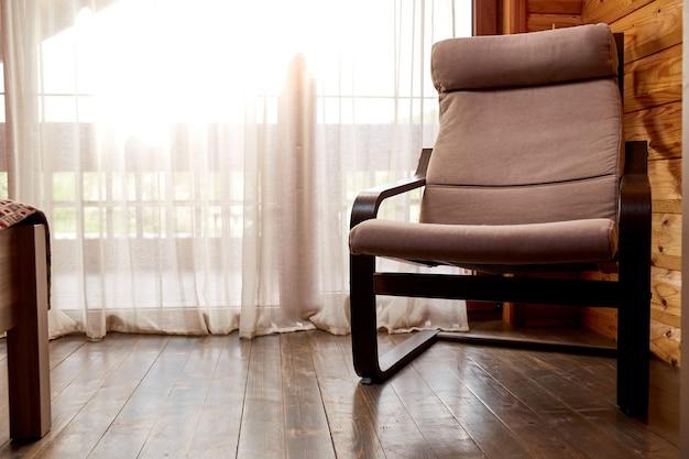 Interieur van houten huis. comfortabele stoel bij raam met elegante gordijnen in de kamer