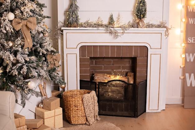 Interieur van kamer met rustieke open haard met geschenken en versierde kerstboom met gloeiende slinger