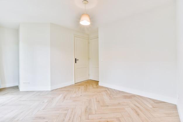 Interieur van leeg modern appartement met geometrisch ontwerp met toegangsdeur en witte muren en parketvloer verlicht met lamp