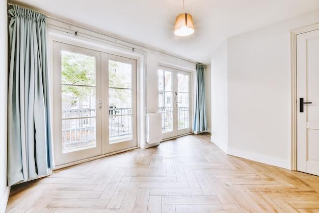 Interieur van lege witte kamer met grote balkonramen met gordijnen en houten parketvloer