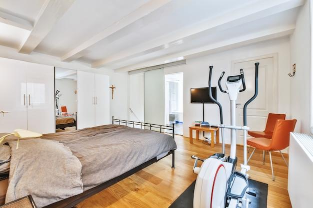 Interieur van lichte hoofdslaapkamer met kleerkasten en crosstrainer bij raam bij daglicht
