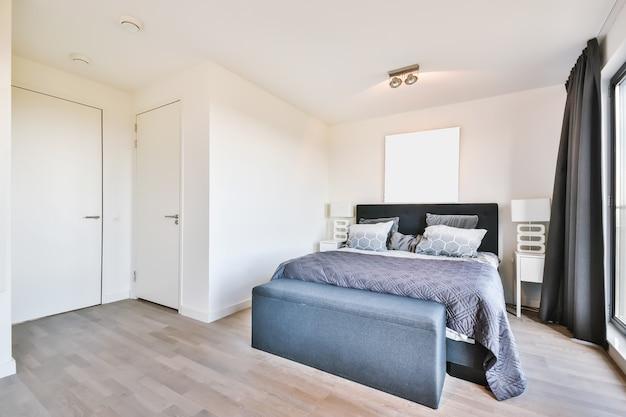 Interieur van lichte slaapkamer met queen size bed en klassieke fauteuil tegen grote ramen