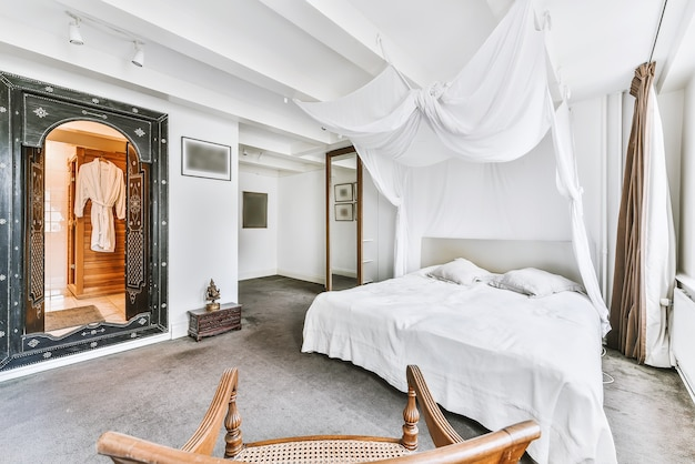 Interieur van lichte slaapkamer met vloerbedekking en witte luifel boven groot bed bij zacht daglicht