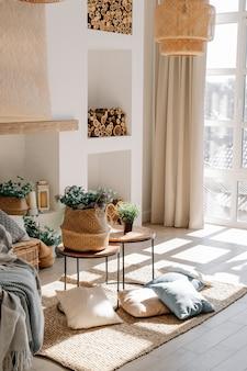 Interieur van lichte woonkamer in scandinavische eco-stijl met salontafel en kussens op de vloer, grote schaduw van raam op de vloer.