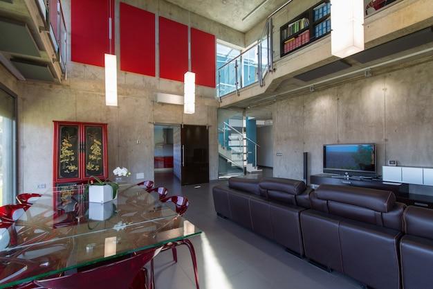 Interieur van modern huis, eetkamer met glazen tafel en rode methacrylaat stoelen, dubbele hoogte.