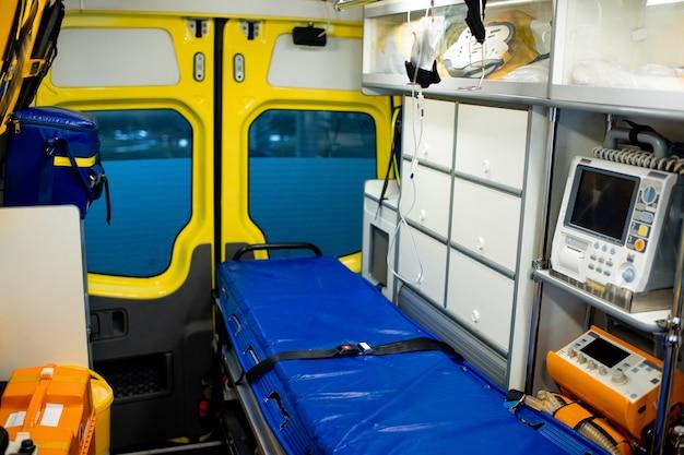 Interieur van moderne ambulanceauto met brancard, druppelaar, ehbo-koffers, koelkast en medische apparatuur