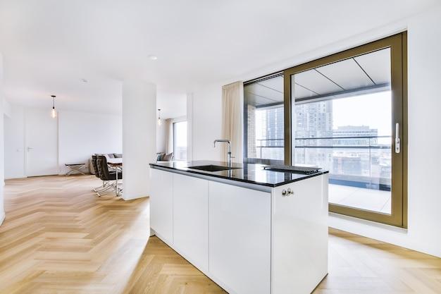 Interieur van moderne keuken in minimalistische stijl met kookeiland en gootsteen in moderne flat