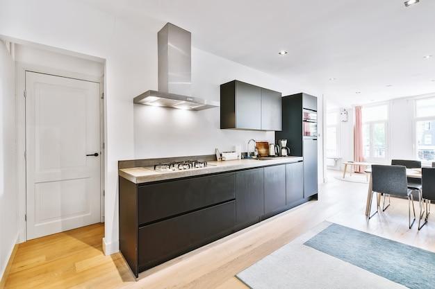 Interieur van moderne keuken met stijlvolle zwarte kasten en inbouwapparatuur bij eethoek in modern appartement