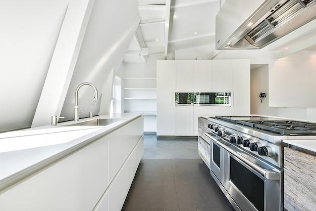 Interieur van moderne keuken met wit meubilair en glanzende toestellen in flat
