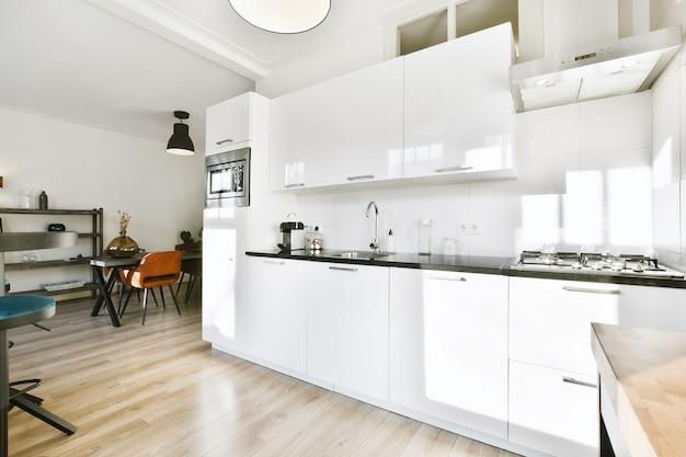 Interieur van moderne ruime keuken in minimalistische stijl met wit meubilair in flat