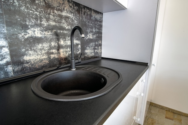 Interieur van moderne ruime keuken met wit eigentijds meubilair, zwarte keramische tegels op de muur en donkere granieten spoelbak met waterkraan.