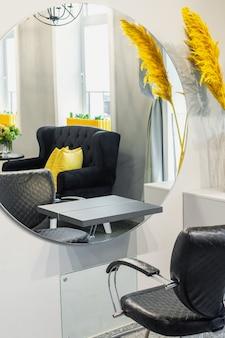 Interieur van moderne schoonheid en kapsalon met fauteuil en spiegel in gele en zwarte tinten.